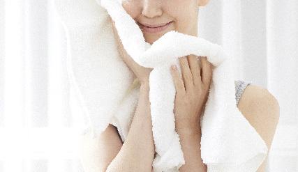 洗顔後タオルに包まれる女性